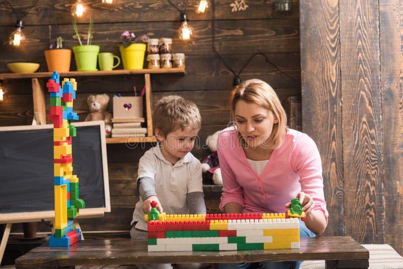 Barnkammare med leksaker och den svart tavlan p? bakgrund Familj som spelar med den hemmastadda konstrukt?rn Moder- och barnlek m royaltyfri foto