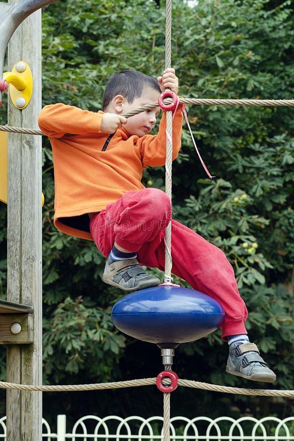 Barnklättring på lekplatsen royaltyfri bild