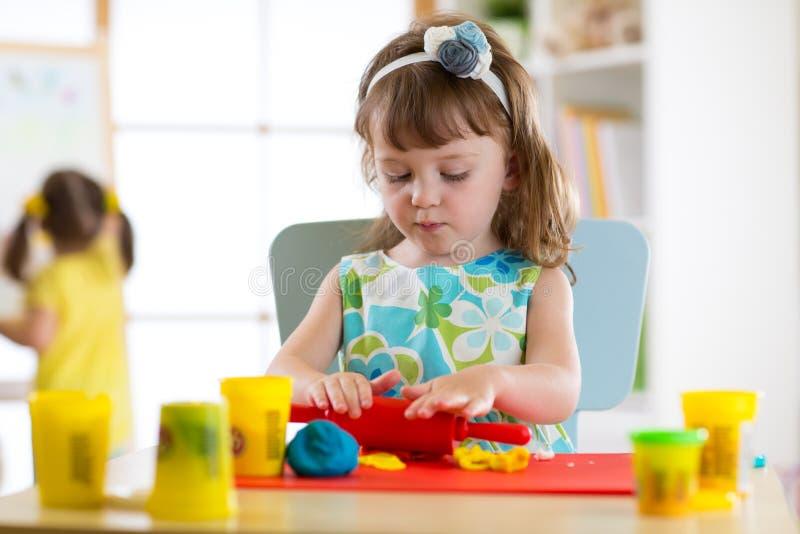 Barnkreativitet Ungar som hugger från lera eller från plasticine och målar i dagis arkivfoton