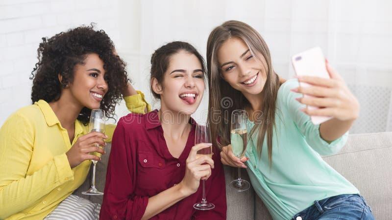 Barnkvinnor som tar selfie och dricker champagne royaltyfria foton
