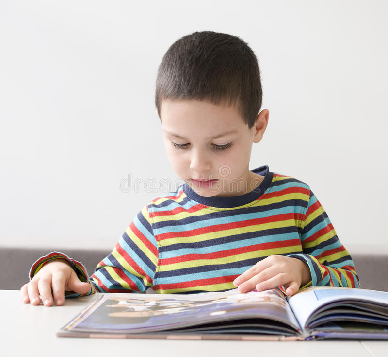 Barnläsning en boka royaltyfria bilder