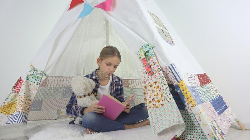 Barnläsning som studerar i lekrum, unge som spelar på lekplatsen som lär flickan arkivbilder