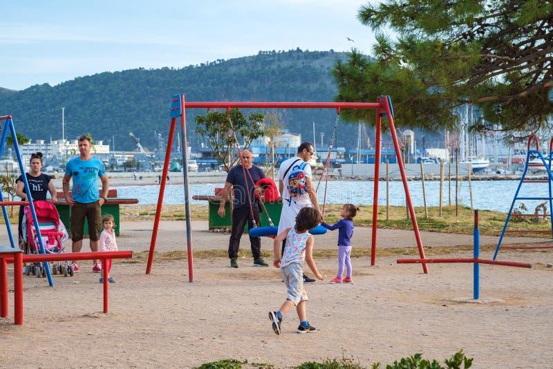 Barnlek i solig sommarstad parkerar på sjösidan royaltyfri foto