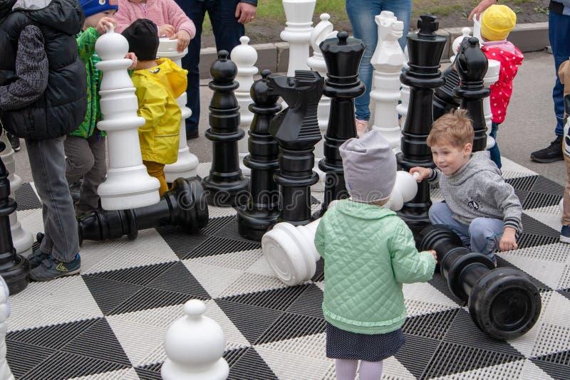 Barnlek med jätte- schackstycken på en stor schackbräde arkivbild