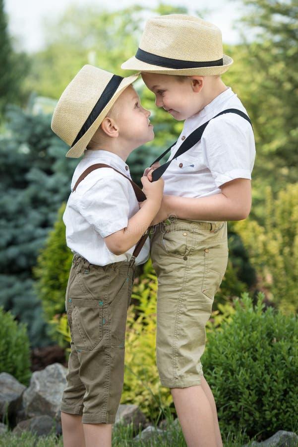 Barnlek, två bröder Den stora kraftmätningen med unga pojkar fotografering för bildbyråer