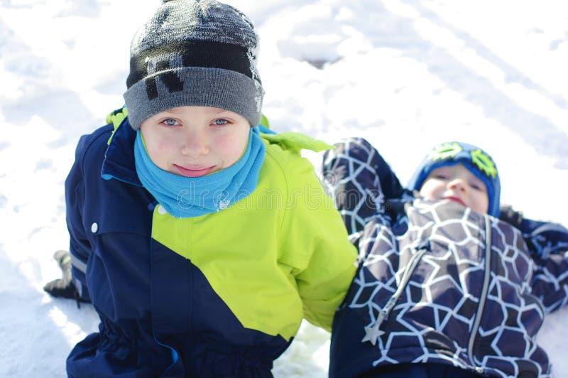 Barnlek utomhus i snö Lyckliga pojkar som spelar på en vinter, går i natur royaltyfri bild