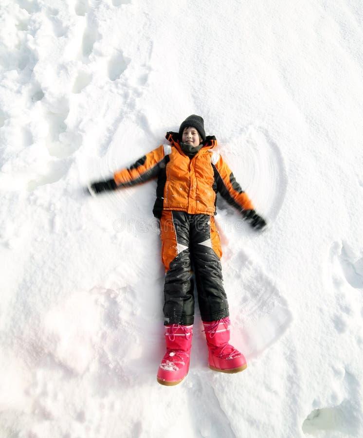 Barnlekar i snön och honom gör formen av ängeln royaltyfri fotografi
