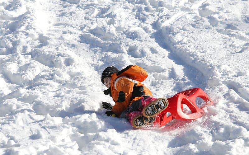 Barnlekar med släden i snön arkivbilder