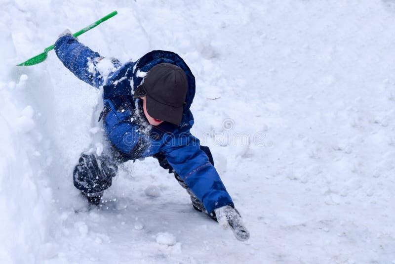 Barnlekarna en snöninja, pojken hoppade från snödrivan royaltyfri bild