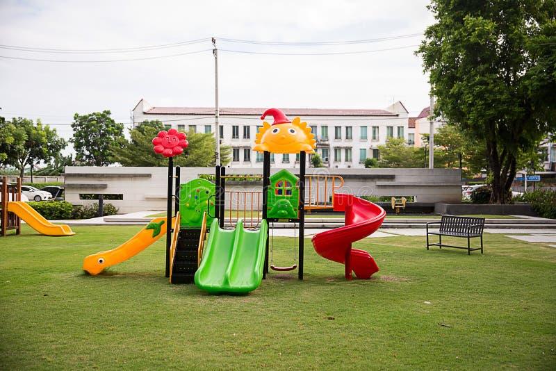 Barnlekplatsen på gårdactivitie parkerar offentligt rundat vid det gröna trädet på solljusmorgonen fotografering för bildbyråer