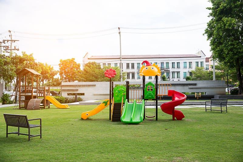 Barnlekplatsen på gårdactivitie parkerar offentligt rundat vid det gröna trädet på solljusmorgonen royaltyfria bilder