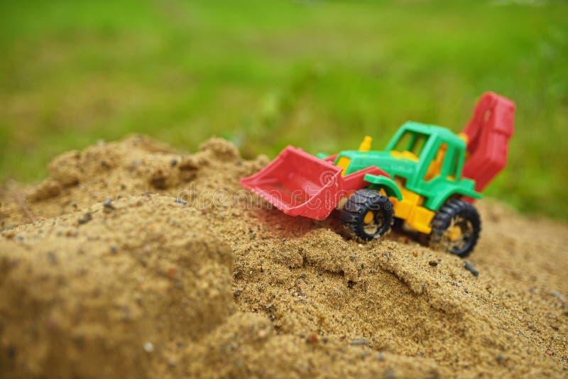 Barnleksaktraktor i sandlåda fotografering för bildbyråer
