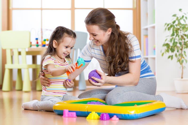 Barnliten flicka och moder som spelar med hemmastadd kinetisk sand royaltyfria foton