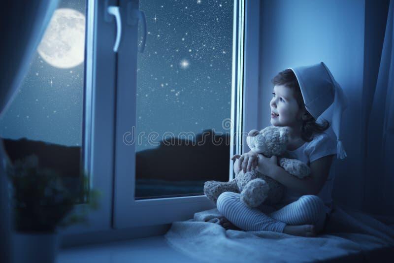 Barnliten flicka på fönstret som drömmer och beundrar den stjärnklara himlen royaltyfria foton