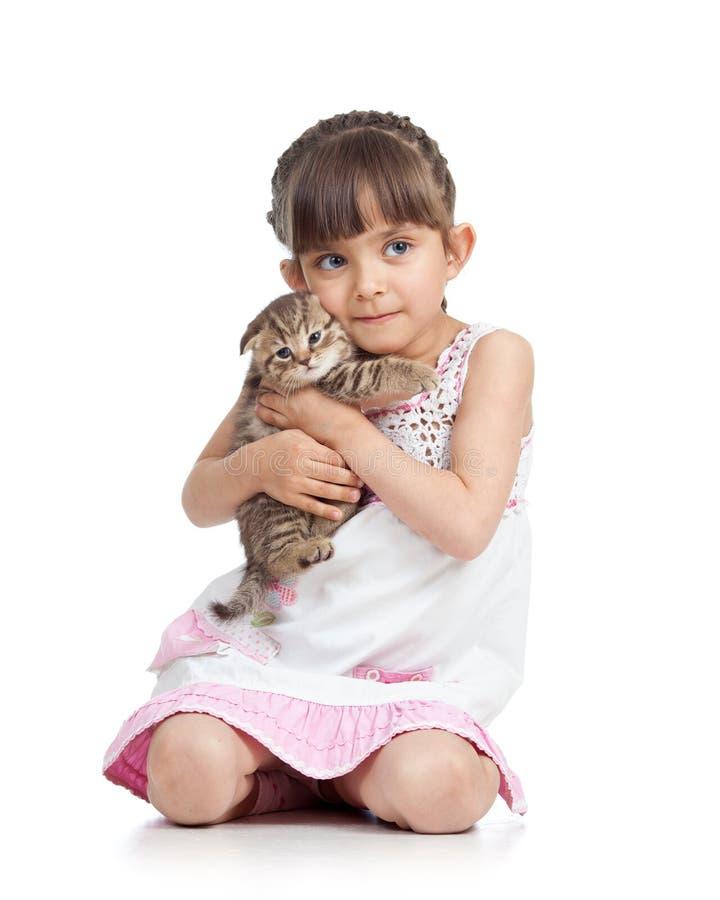 Barnliten flicka som kramar kattungen bakgrund isolerad white fotografering för bildbyråer