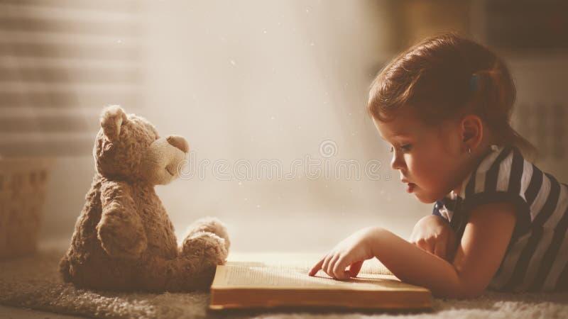 Barnliten flicka som läser en magisk bok i mörkerhem fotografering för bildbyråer