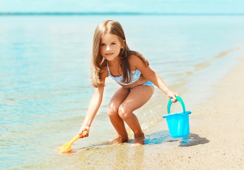 Barnliten flicka som spelar med leksaker på stranden i vattenhavet i solig sommar royaltyfri bild