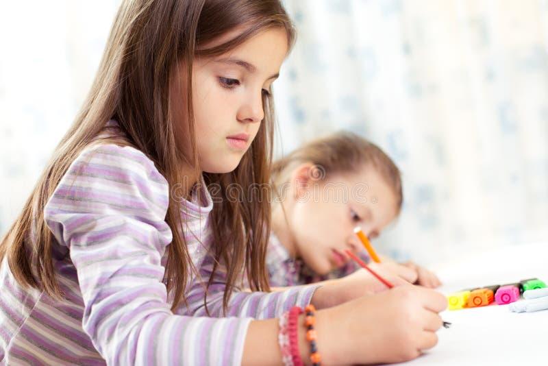 Barnmålning på stafflin i skola royaltyfri foto