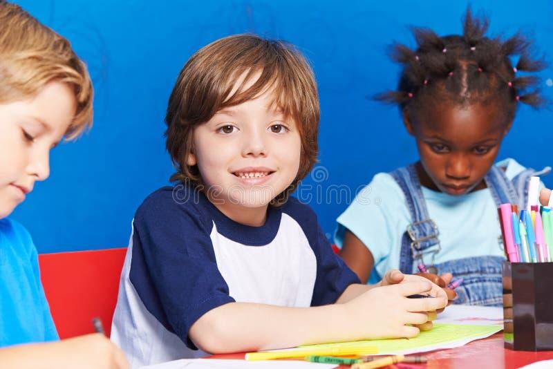 Barnmålningbild på tabellen i dagis arkivfoton