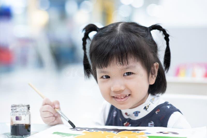 Barnmålningfärg genom att använda borsten på papper tyck om, le, lyckligt, klyftigt och dröm- fotografering för bildbyråer