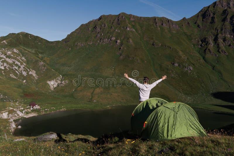 Barnmannens armar lyftte framme av ett grönt tält i bergen av Schweiz, medan han tycker om panoramautsikten arkivfoto