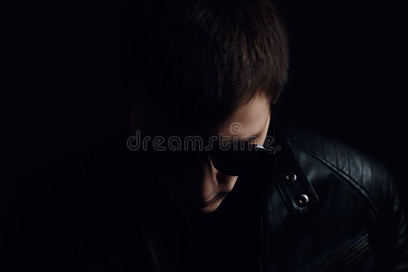 Barnmans st?ende Närbilden av den allvarliga unga mannen i en svart piskar omslaget och solglasögon arkivbild