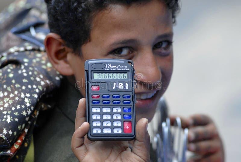 Barnmarknadssäljaren visar räknemaskinen för att köpslå priset i Sana'a, Yemen arkivfoto