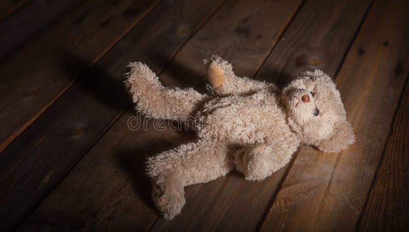 Barnmisshandel Nallebjörn på golvet, mörk träbakgrund royaltyfri fotografi