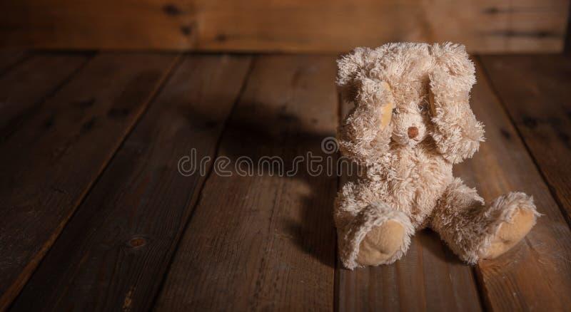 Barnmisshandel Nallebjörn som täcker ögon, mörk tom bakgrund, kopieringsutrymme arkivbilder