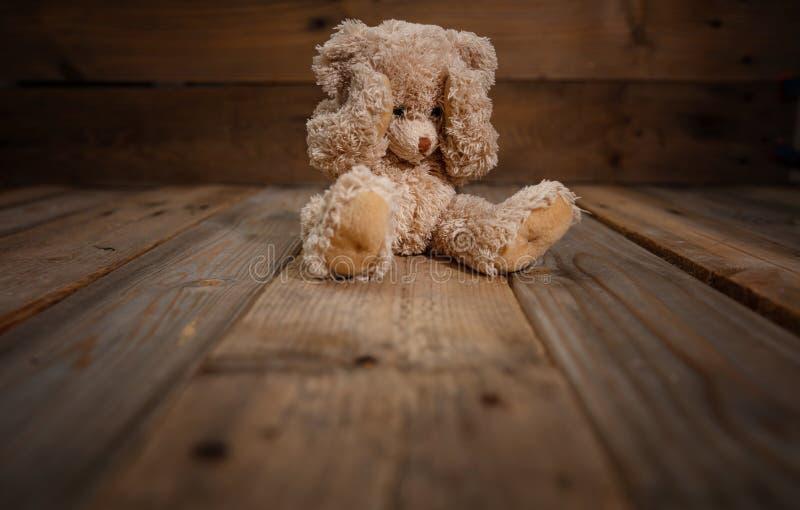 Barnmisshandel Nallebjörn som täcker ögon, mörk tom bakgrund, kopieringsutrymme arkivbild