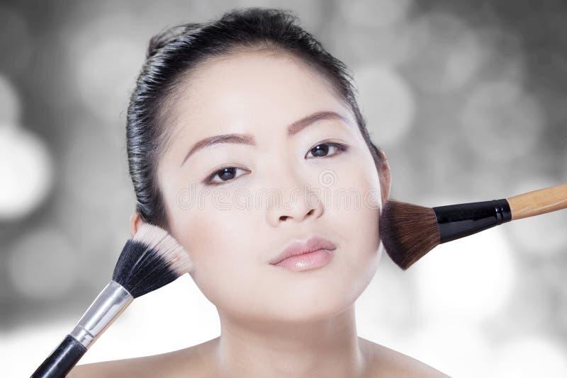 Barnmodell med makeupborsten arkivfoto