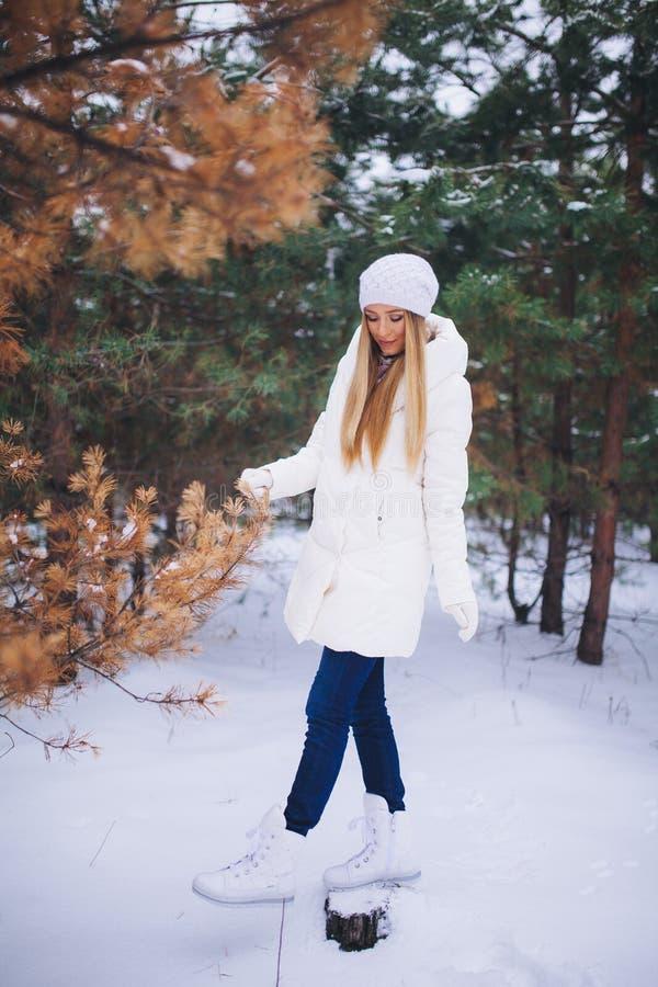 Barnmodellflickan går i vinterskogen royaltyfri foto