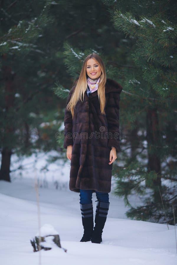 Barnmodellflickan går i vinterskogen royaltyfria bilder