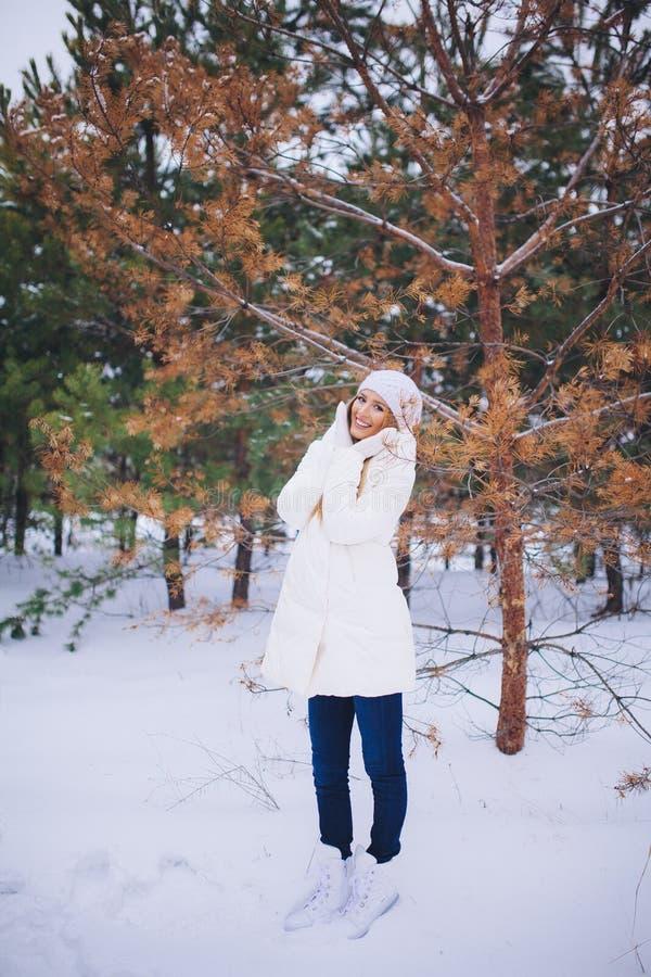Barnmodellflickan går i vinterskogen fotografering för bildbyråer