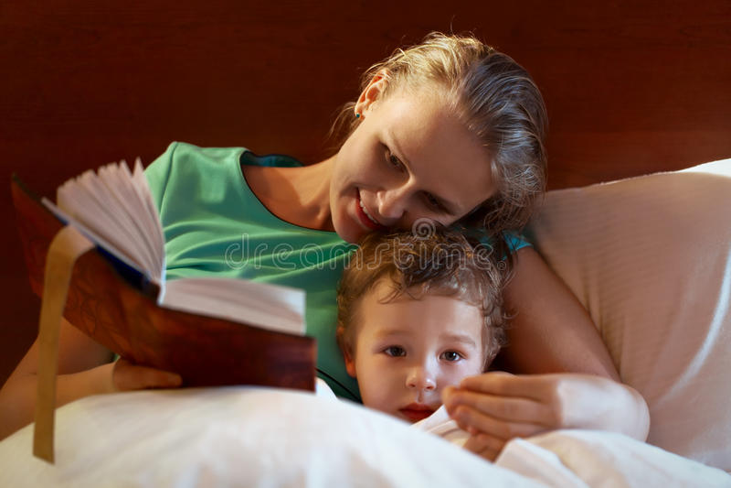 Barnmoder som läser till hennes barn i säng royaltyfri bild