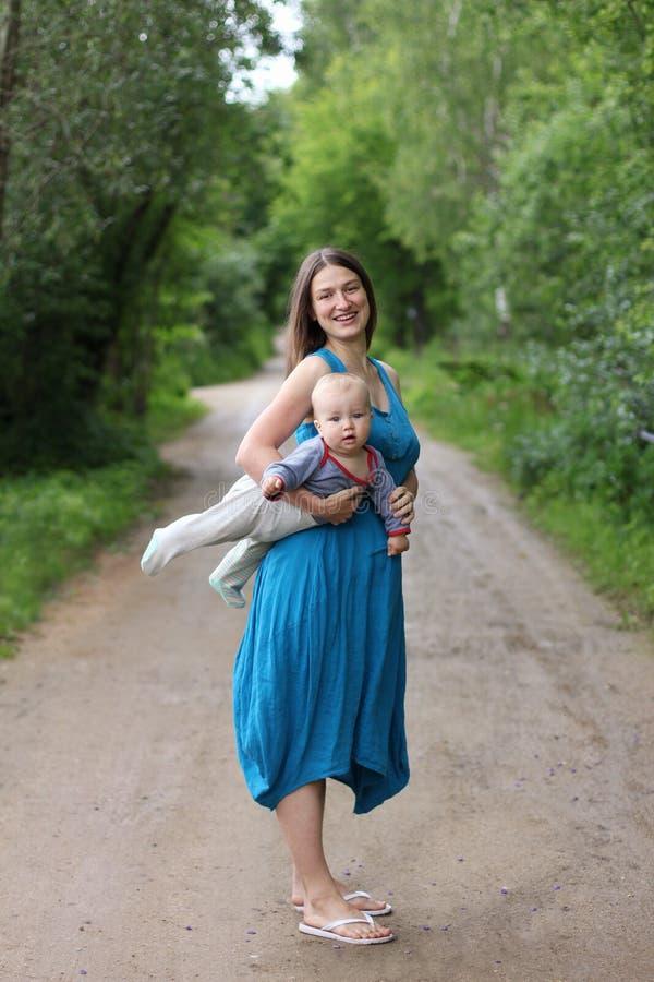 Barnmoder som rymmer den lilla sonen under hennes arm royaltyfri foto