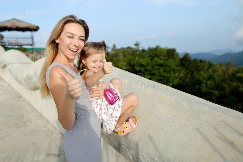 Barnmoderanseende med den lilla dottern i Phuket, visningtummar upp royaltyfri foto
