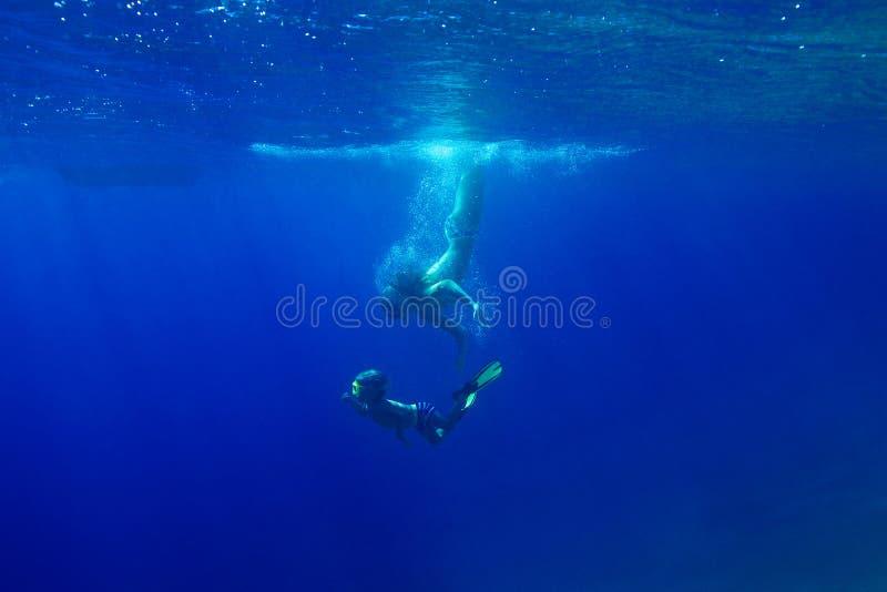Barnmodern dyker under vattnet i havet med hans son FN fotografering för bildbyråer