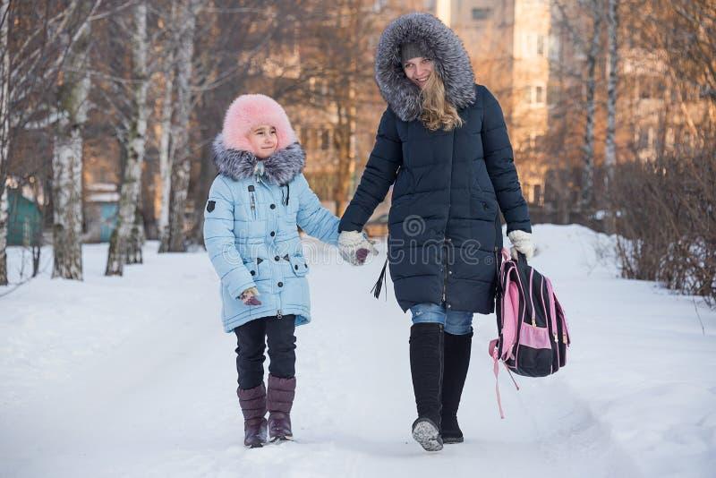 Barnmodern leder dottern från skola royaltyfri foto