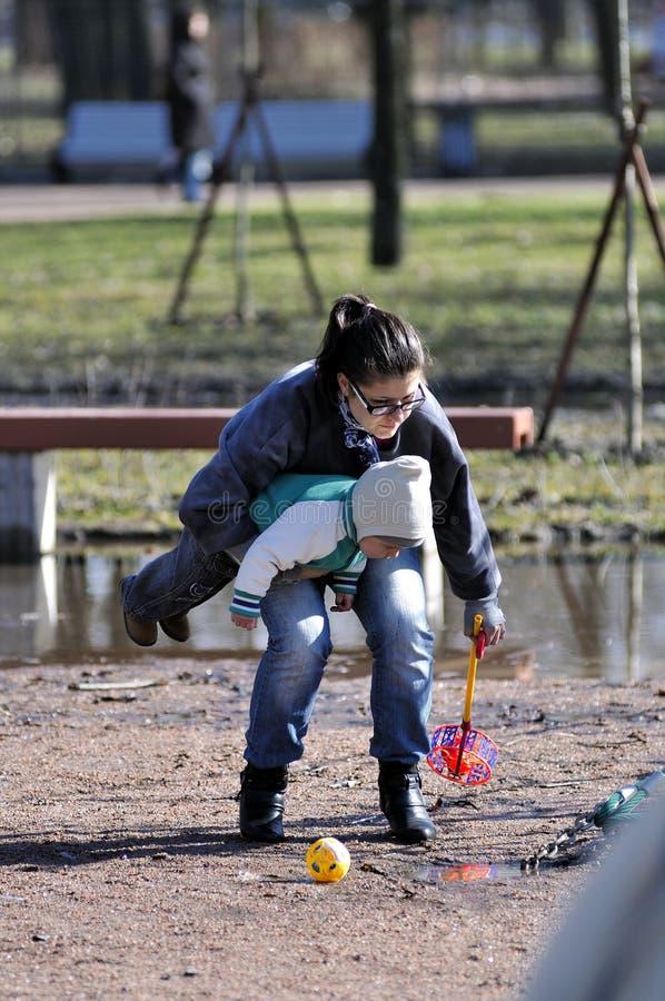 Barnmodern rymmer barnet när försök att lyfta leksaken royaltyfri bild