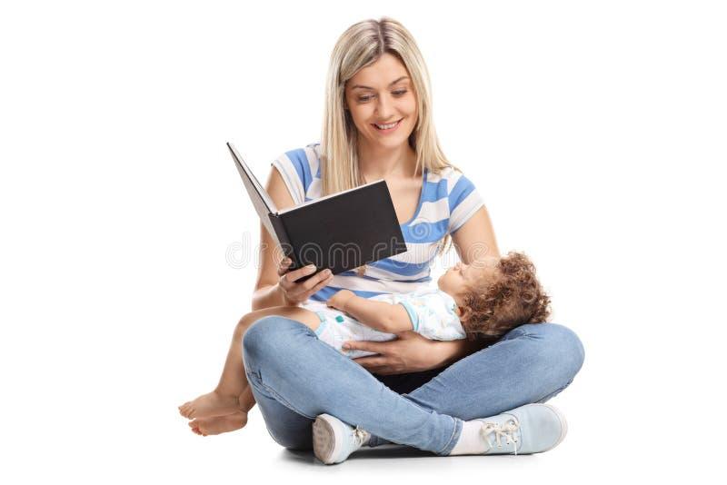 Barnmodern som läser en bok med hennes, behandla som ett barn pojken som sover i hennes la royaltyfria foton