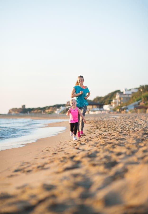 Barnmoderspring bak dotter på stranden på solnedgången arkivbilder