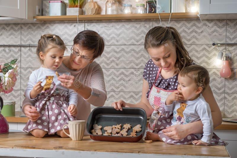 Barnmormor och två flickor lagar kakor royaltyfria foton