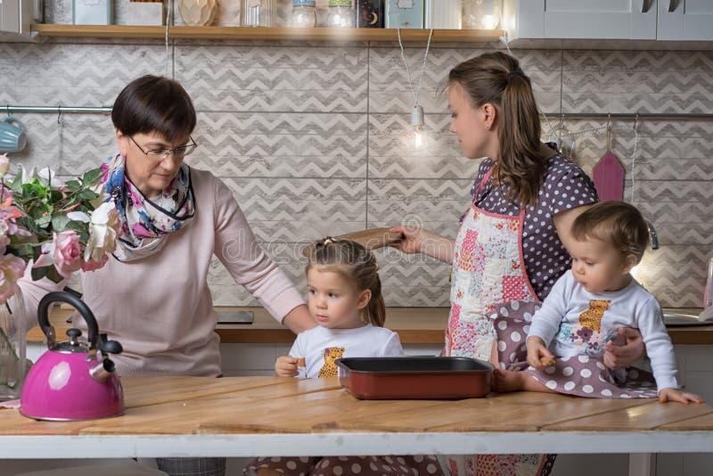 Barnmormor och två flickor lagar mat royaltyfria foton