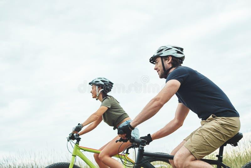 Barnpar cyklar på fatbikes och i hjälmar Kantjusterat foto arkivbild