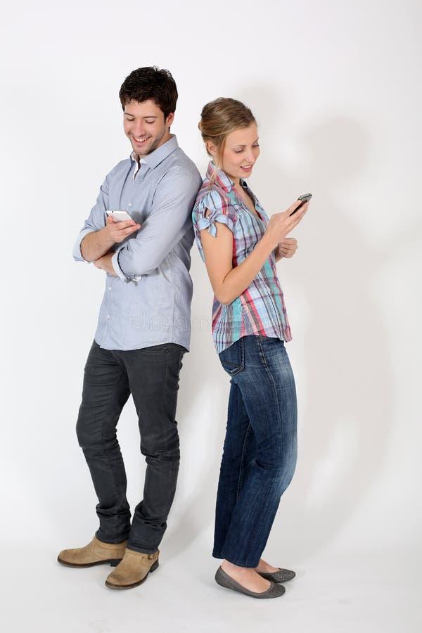 Barnpar genom att använda smartphones som står isolerade arkivfoton