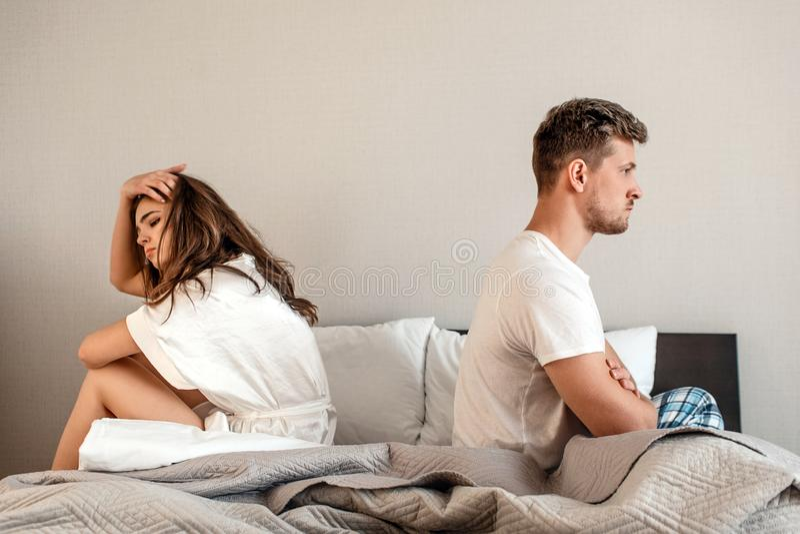 Barnpar i sovrummet Den olyckliga mannen och kvinnan sitter tillbaka för att dra tillbaka i sängen, par grälar hem- plats royaltyfri foto