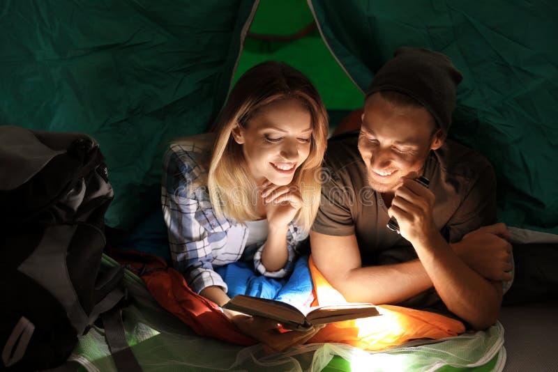 Barnpar i sovsäckläsebok arkivfoton