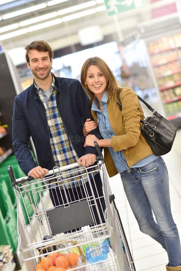 Barnpar med shoppingteburken i supermarket royaltyfri fotografi
