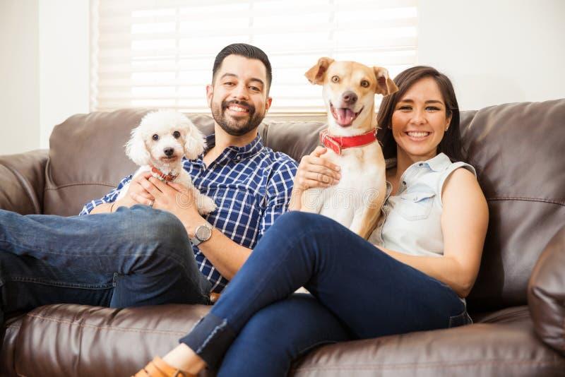 Barnpar med två hundkapplöpning hemma royaltyfria foton